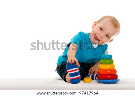 A little boy is playing with toys on the blanket; isolated on the white background - stock photo