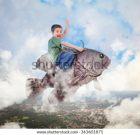 A little boy is riding a fish in the sky with a city below and clouds for an imagination, happiness or freedom concept. - stock photo