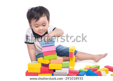 A little boy is sitting on the floor near toys. kid playing with building blocks toy - stock photo