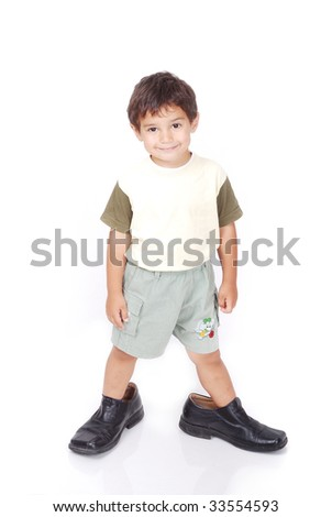 A little boy is standing in adult shoes