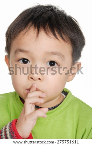 A little boy keeping silence by covering his mouth by hands - stock photo