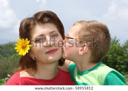 A little boy kisses his mom - stock photo