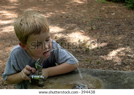 a little boy laping water from a drinking fountain in the park. - stock photo