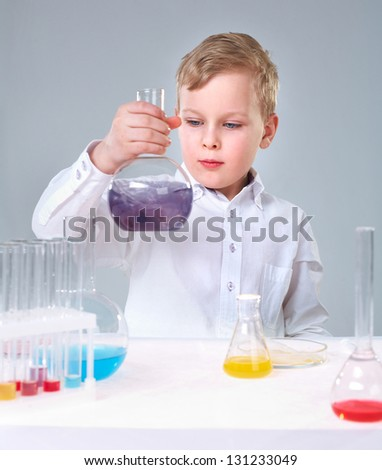 A little boy looking at liquid in flask - stock photo