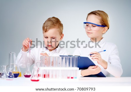 A little boy mixing chemical liquids and his assistant making notes - stock photo