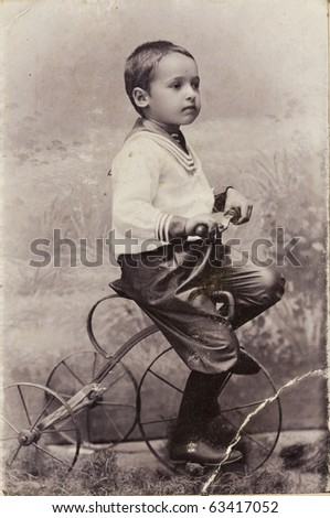 A little boy on a bicycle, old photo - stock photo