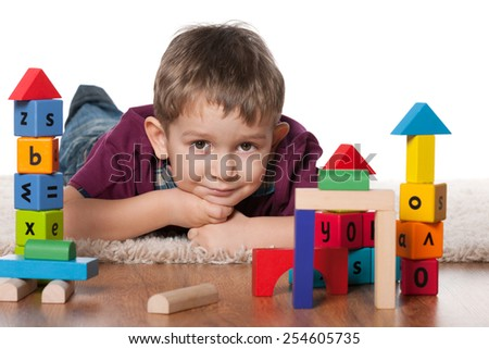 A little boy plays with toys on the floor - stock photo