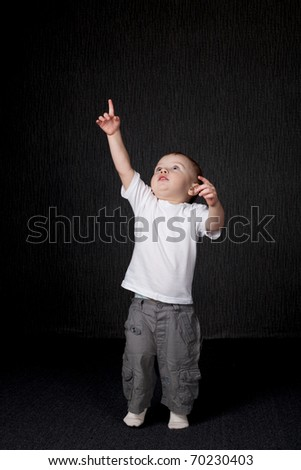 a little boy points up - stock photo