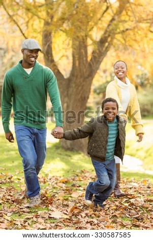 A little boy pulling his parents to walk more quickly on an autumns day - stock photo