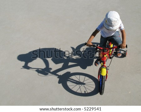 A little boy riding a bike with his shadow on a gray background - stock photo