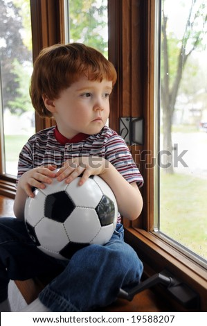 A little boy sits by a window on a rainy day, wishing he could go outside and play soccer - stock photo