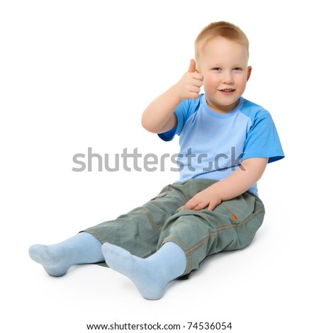 A little boy sits on a white background showing a gesture thumb up - stock photo