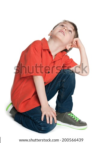 A little boy sits on the floor and looks up - stock photo