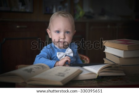 A little boy sitting at a table with books