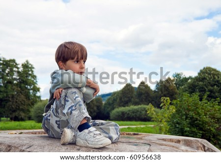 A little boy sitting on a felled tree - stock photo