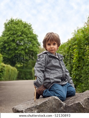A little boy sitting on a rock. - stock photo