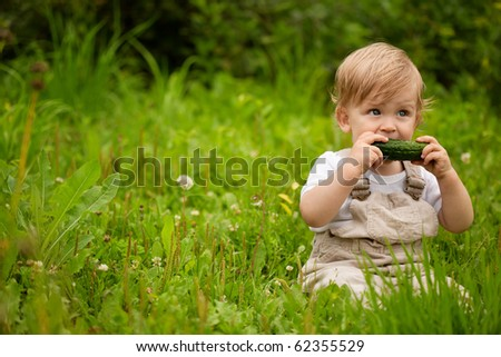 A little boy sitting on the grass and chews cucumber. - stock photo