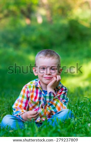 A little boy sitting on the grass, smiling and head support arm. Family composition - stock photo
