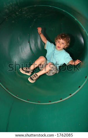 A little boy slides around the bend in a big green tube tunnel slide.