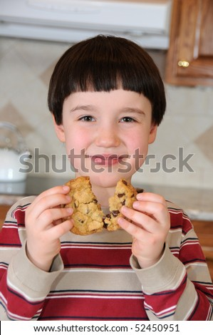 A little boy smiles as he breaks a chocolate chip cookie before eating it