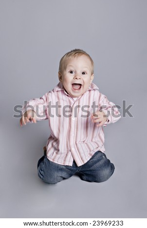 a little boy smiles upright on knees