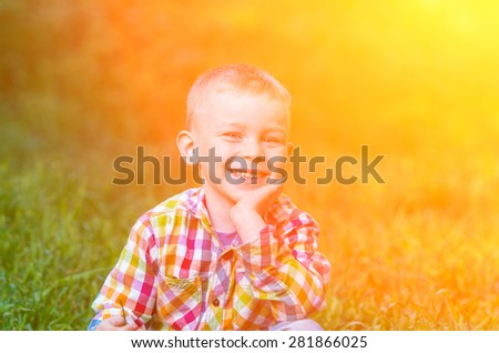 A little boy smiling and hand supports the head when it is backlit. Family composition - stock photo