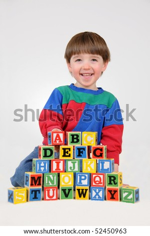 A little boy spells the alphabet out of letter blocks - stock photo