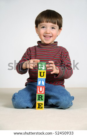 A little boy spells the word 'future' out of letter blocks - stock photo