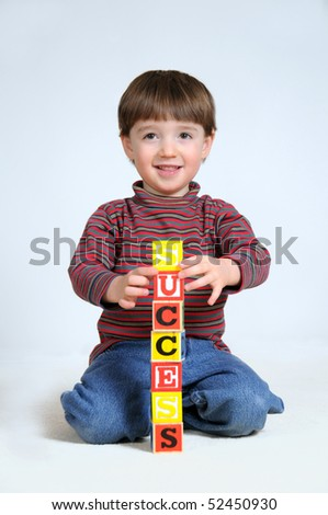 A little boy spells the word 'success' out of letter blocks - stock photo