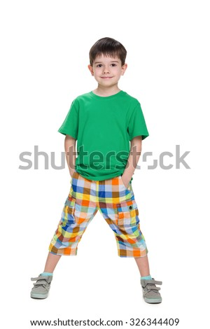 A little boy stands against the white background