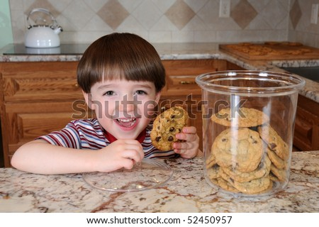 A little boy steals a chocolate chip cookie from a cookie jar in his mother's kitchen - stock photo