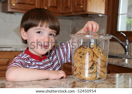 A little boy steals chocolate chip cookies from a cookie jar in his mother's kitchen - stock photo
