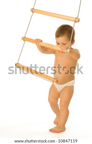 A little boy trying to climb a rope-ladder - stock photo