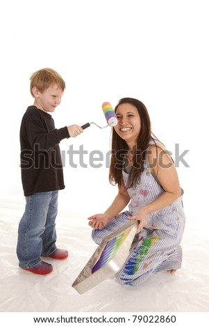 a little boy using a rainbow colored roller painting a womans face with it.