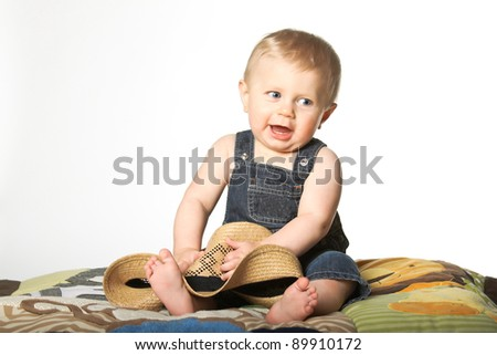 A little boy wearing a farmer's outfit and holding a straw hat in his hands. - stock photo