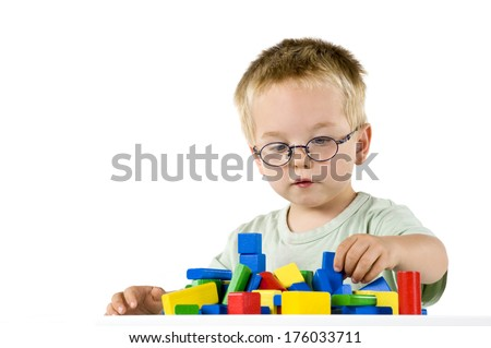 A little boy wearing round glasses playing with colored blocks. - stock photo