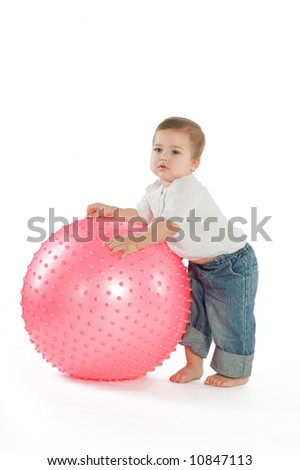 A little boy with a big pink fitness ball - stock photo