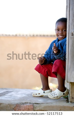 A little boy with a big smile wearing a blue jumper and red shorts holding a toy in one hand and giving a thumbs up with the other - stock photo