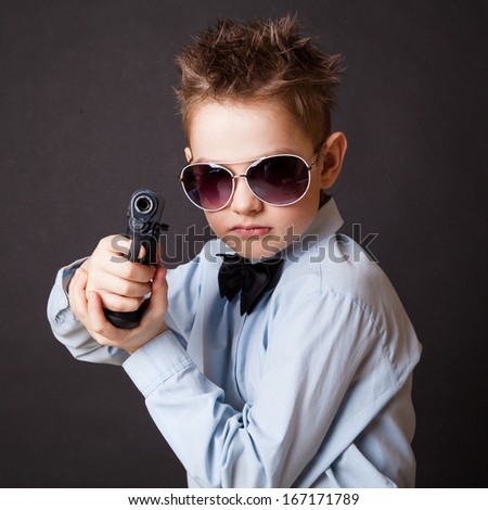 A little boy with a weapon on a black background