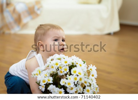 a little boy with white flowers at home - stock photo