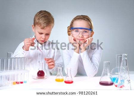 A little boy working with liquid and his assistant looking at camera - stock photo
