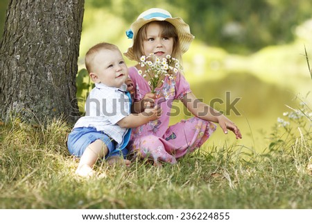 a little brother and sister playing on the nature