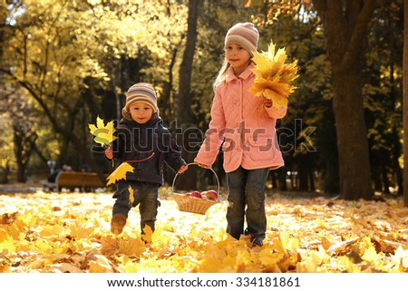 a little brother and sister playing outdoors in autumn park - stock photo