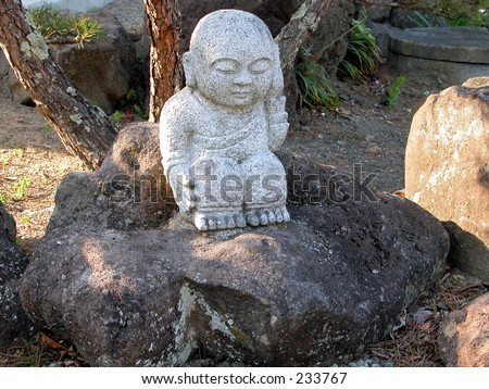 A Little Buddhist Rock Statue In A Japanese Rock Garden
