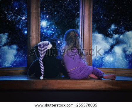 A little child and her teddy bear are looking outside a window with space stars and clouds in the night for a astronomy or dream concept. - stock photo