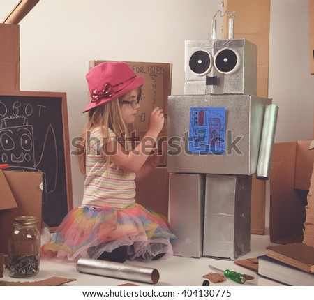 A little child is building and fixing a robot with boxes and tools for a girl power, education or imagination concept. - stock photo