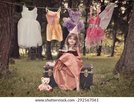 A little child is dressed up as a princess reading a book in the woods with costumes hanging from a clothesline for an education or fairytale concept. - stock photo