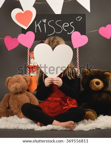 A little child is holding a white paper heart with a Kiss Booth stand behind her with teddy bears for a Valentine concept. - stock photo