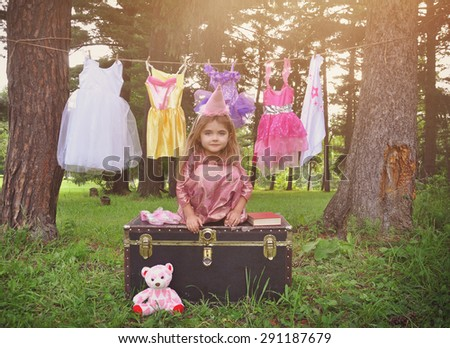 A little child is pretending to be a princess outside with dress up clothes hanging on a clothesline for a imagination or creativity concept. - stock photo
