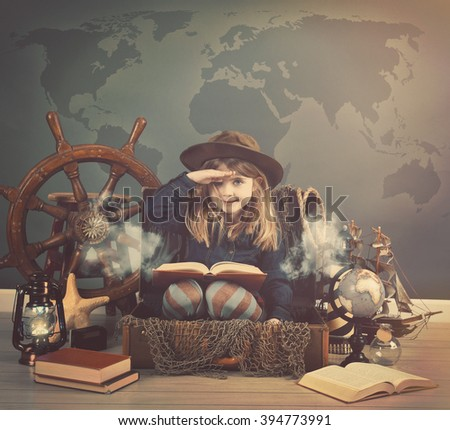 A little child is pretending to sail in a suitcase boat and holding a vintage story book with sea objects for an exploration or imagination concept. - stock photo